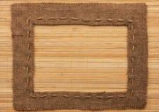 Frame of burlap, lies on a bamboo mat Stock Image