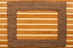 Frame of burlap, lies on a bamboo mat Royalty Free Stock Photo