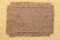 Frame of burlap  lying on a millet  background Royalty Free Stock Photos