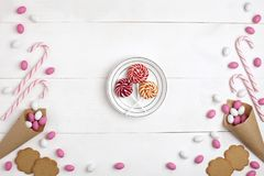 Frame Candies, cookies, Marshmallows and Lollipops on plate Top view White wooden Background. Frame colorful Candies, Striped Lollipops, cookies, Marshmallows stock photography