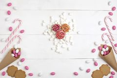 Frame Candies, cookies,Marshmallows and Lollipops Top view White wooden Background. Frame colorful Candies, Striped Lollipops, cookies, Marshmallows and Stock Photo