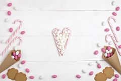 Frame Candies, Marshmallows, cookies and Striped Lollipops in the form of heart Top view White wooden Background. Frame colorful Candies, Marshmallows, cookies royalty free stock photography
