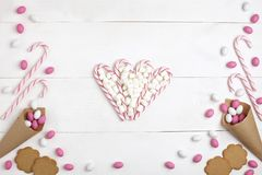 Frame Candies, Marshmallows, cookies and Striped Lollipops in the form of heart Top view White wooden Background. Frame colorful Candies, Marshmallows, cookies royalty free stock images