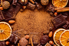 Frame of chocolate truffles, chocolate bars and other sweets. Chocolate bars, candies, truffles, praline, nuts and dried orange rings frame. Copy space for text royalty free stock photography