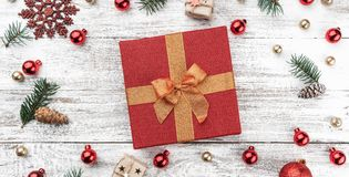 Frame on christmas background of old wood. Red and gold Baubles. Fir branches and cones. In the center a red gift. Xmas items. Top view. Horizontally Xmas card royalty free stock photography