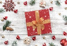 Frame on christmas background of old wood. Red and gold Baubles. Fir branches and cones. In the center a red gift. Xmas items. Top view. Snow effect royalty free stock photo