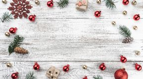 Frame on christmas background of old wood. Red and gold Baubles. Fir branches and cones. Xmas items. Top view. Horizontally Xmas card stock image