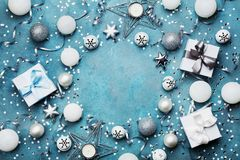 Frame of christmas decoration, gift box, confetti and silver sequins on vintage blue table top view. Flat lay. Party mockup. Stock Image