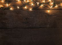 Frame of Christmas lights on old wooden desk background and empty space for text. Top view with copy space.  royalty free stock photo