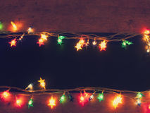 Frame of Christmas lights on wooden table Royalty Free Stock Images