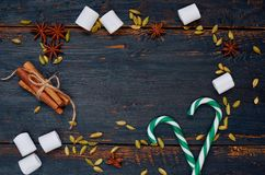 Frame of Christmas or New year food decorations - marshmallows, green candy cones, traditional winter spices - cinnamon, cardamom royalty free stock photos