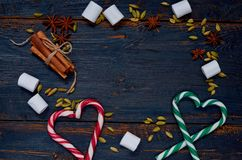 Frame of Christmas or New year food decorations - marshmallows, hearts of candy cones, traditional winter spices stock photo