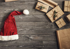 Frame of Christmas Present and santa hat on wooden table Royalty Free Stock Image