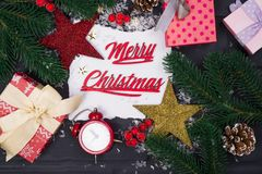 Frame of Christmas tree branches, gift boxes, red clocks and Christmas toys around a white sheet of paper royalty free stock image