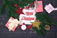 Frame of Christmas tree branches, gift boxes, red clocks and Christmas toys around a white sheet of paper royalty free stock photography