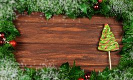 Frame of Christmas tree branches with toys on a wooden backgroun. D with a candy in the form of a Christmas tree in green and snow for the new year Royalty Free Stock Photography