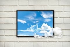 Frame with clouds and blue sky on a white brick wall, think outside the box concept stock images