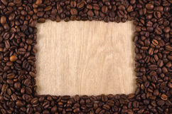 Frame. Coffee beans forming a rectangle on a wooden table. Place in the center for your text / design Stock Photo