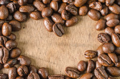 frame Coffee beans heart shaped on wood background Royalty Free Stock Photos