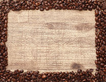 Frame Of Coffee Beans. Coffee beans lined up around a wood background to create a frame or copy space.  Would make a unique chalkboard writing space as well Stock Photo