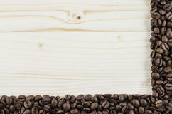 Frame of coffee beans on wooden table. Background Royalty Free Stock Images