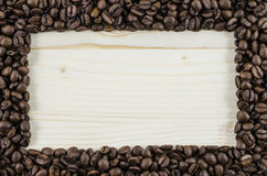 Frame of coffee beans on wooden table. Background Stock Photography