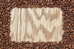 Frame of coffee beans on a wooden texture. Royalty Free Stock Photos