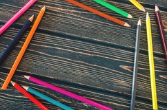 Frame of colored pencils on wooden background royalty free stock photography