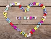Frame of colored wooden letters in shape of heart and text & x22;Be happy& x22;. Frame of colored wooden letters in shape of heart and text & x22;Be Stock Images