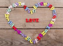 Frame of colored wooden letters in shape of heart and text & x22;Love& x22; Stock Photo