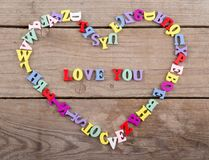 Frame of colored wooden letters in shape of heart and text & x22;Love you& x22; Royalty Free Stock Photo