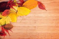 Frame of colorful autumnal leaves, wood background Stock Photo
