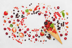 Frame with colorful berries in waffle cone on light background top view. Dietary and healthy dessert. Flat lay styling. Stock Photography