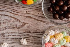 Frame of colorful bright assorted candy in bowls and jars, candy canes and rainbow colored spiral lollipops on black with scattere Stock Photos