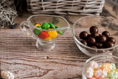 Frame of colorful bright assorted candy in bowls and jars, candy canes and rainbow colored spiral lollipops on black with scattere Royalty Free Stock Image