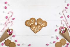 Frame Candies and cookies in the form of heart Top view White wooden Background. Frame colorful Candies, Striped Lollipops and cookies in the form of heart in royalty free stock images