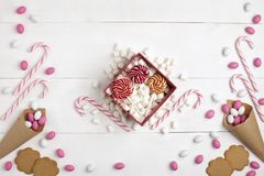 Frame Candies, cookies,Marshmallows and Lollipops Gift Top view White wooden Background. Frame colorful Candies, Striped Lollipops, cookies, Marshmallows and stock photo
