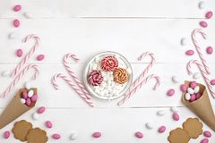 Frame Candies, cookies,Marshmallows and Lollipops on plate Top view White wooden Background. Frame colorful Candies, Striped Lollipops, cookies, Marshmallows and stock images