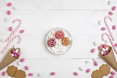 Frame Candies, cookies,Marshmallows and Lollipops on plate Top view White wooden Background. Frame colorful Candies, Striped Lollipops, cookies, Marshmallows and royalty free stock photos