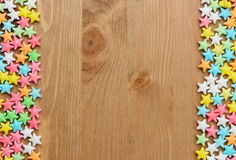 Frame of colorful candy stars on wood background Stock Image