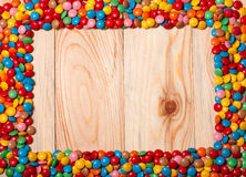 Frame of colorful candy on wood background Royalty Free Stock Photography