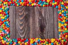 Frame of colorful candy on wood background Stock Images