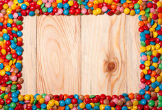 Frame of colorful candy on wood background Stock Image