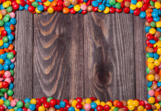 Frame of colorful candy on wood background Stock Photos