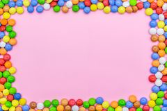 A frame of colorful chocolates. Close-up view of the top, pink background royalty free stock photo