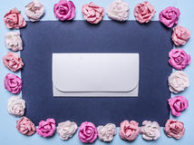 Frame of colorful paper roses, laid out on a dark background with an envelope  middle  top view close up place text Royalty Free Stock Photo