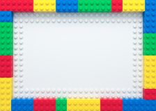 Frame of colorful toy bricks. On white construction plate stock illustration