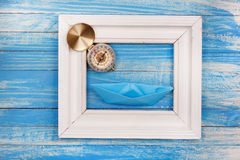 Frame with compass and blue paper boat Royalty Free Stock Photography