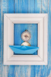 Frame with compass and blue paper boat Stock Photos