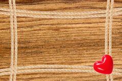 Frame composed of rope and red heart over wooden background Royalty Free Stock Photography